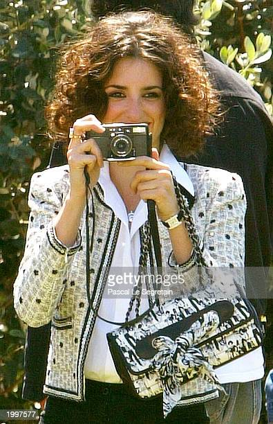 Actress Penelope Cruz takes photographs during a photocall for the film 'Fan Fan La Tulipe' at the Palais des Festivals during the 56th International...