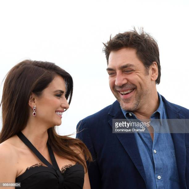 Actress Penelope Cruz wearing jewels by Atelier Swarovski Fine Jewelry smiles with actor Javier Bardem at the photocall for Everybody Knows during...