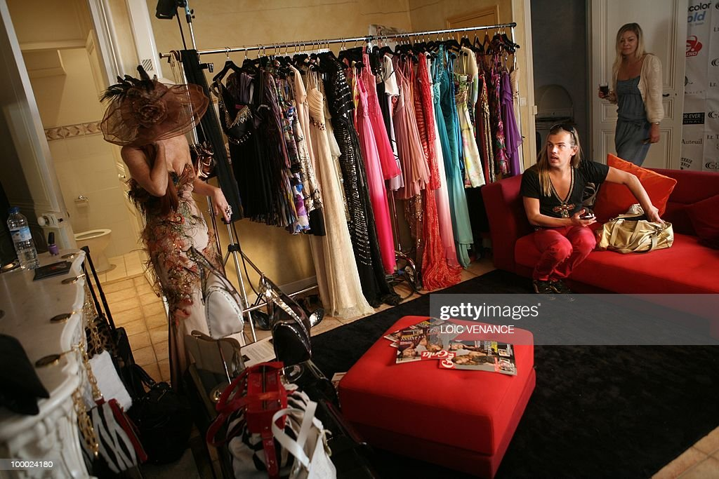 US actress Phoebe Price tries clothes designed by French designer Christophe Guillarme (R) as she prepares to walk on the red carpet at the 63rd Cannes Film Festival on May 20, 2010 in Cannes.