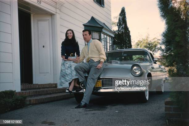 Actress Pier Angeli and husband singer Vic Damone pose for a portrait with their 1956 Ford Thunderbird at home on March 15 1957 in Los Angeles...