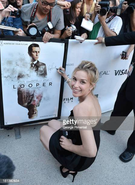 Actress Piper Perabo signs a poster as she attends the 'Looper' opening night gala premiere during the 2012 Toronto International Film Festival on...