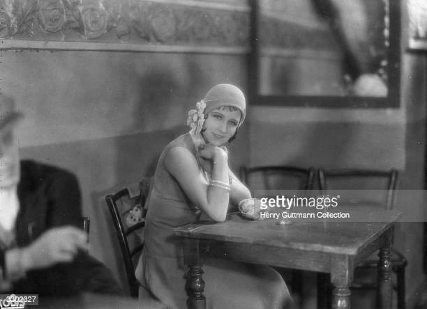 Actress Pola Illery sits alone at a cafe table in a scene from the film 'Sous Les Toits De Paris' an early French talkie directed by Rene Clair