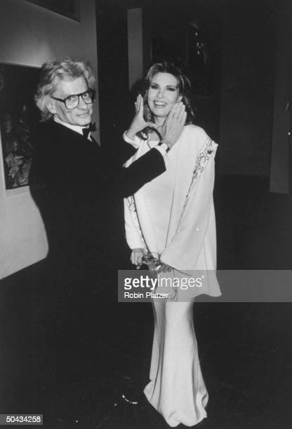 Actress Raquel Welch having her face framed by photographer Richard Avedon's hands at a retrospective of his work presented at the Whitney Museum