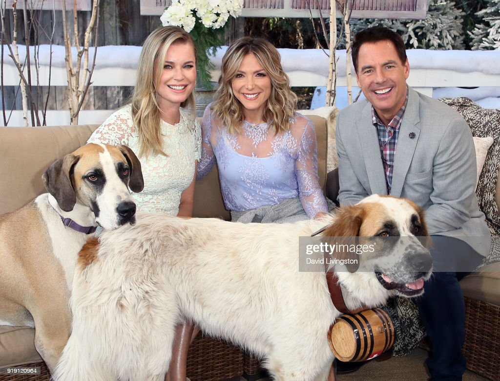 Actress Rebecca Romijn and hosts Debbie Matenopoulos and Mark Steines pose with Romijn's dogs at Hallmark's 'Home & Family' at Universal Studios Hollywood on February 16, 2018 in Universal City, California.