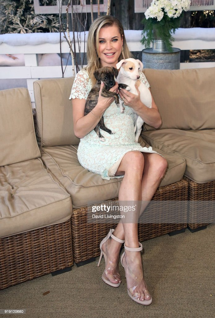 Actress Rebecca Romijn poses with puppies at Hallmark's 'Home & Family' at Universal Studios Hollywood on February 16, 2018 in Universal City, California.