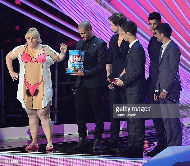 Actress Rebel Wilson and singers Max George Jay McGuiness Nathan Sykes Siva Kaneswaran and Tom Parker of musical group The Wanted speak onstage at...