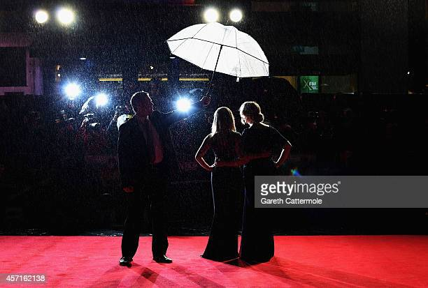 Actress Reese Witherspoon and writer Cheryl Strayed are given shelter from the rain as she attends The May Fair Hotel Gala VIP arrivals of Wild...