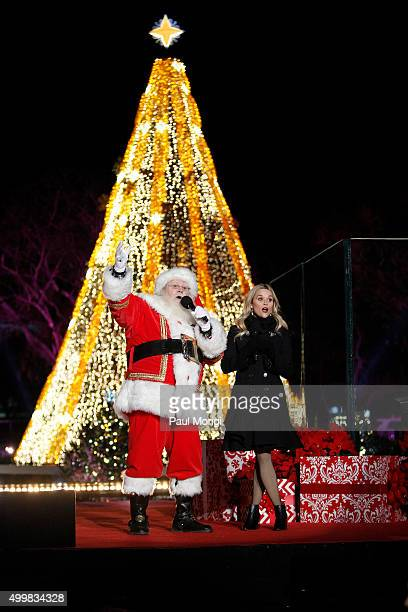 Actress Reese Witherspoon sings Christmas carols with Santa Claus during the 93rd Annual National Christmas Tree Lighting at The Ellipse on December...