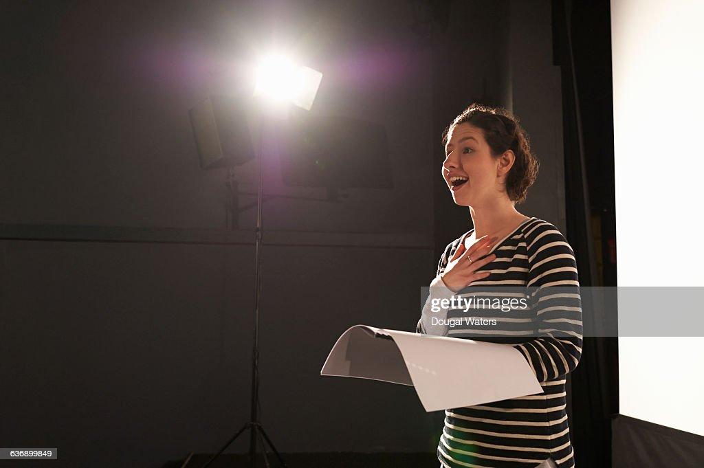Actress rehearsing under spotlight on stage. : Stock-Foto