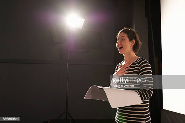 actress rehearsing under spotlight on stage. - rehearsal stock pictures, royalty-free photos & images