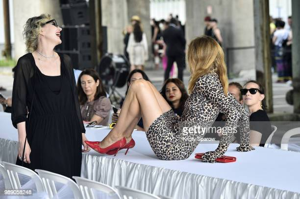 Actress Renata Litvinova laughs as model Natalia Vodianova climbs over the runway before the Vetements Haute Couture Fall Winter 2018/2019 show as...