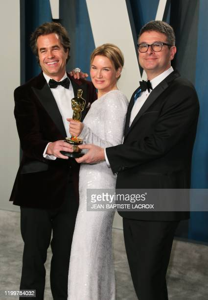 "Actress Renee Zellweger, flanked by producers David Livingstone and director Rupert Goold , holds her Oscar for Best Actress for ""Judy"" as she..."