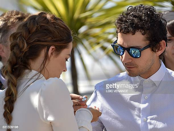 US actress Riley Keough and US actor Shia Labeouf take homeopathic medicine on May 15 2016 during a photocall for the film 'American Honey' at the...