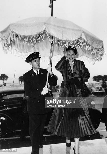 Actress Rita Hayworth having an umbrella held over her as she leaves her car at the Cannes Film Festival, April 24th 1952.