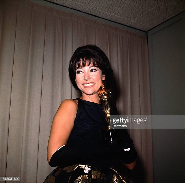 Actress Rita Moreno is shown here smiling as she holds her Academy Award