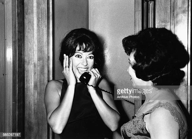 Actress Rita Moreno smiling as she makes a phone call after winning the Best Supporting Actress Oscar for the film 'West Side Story' at the 39th...