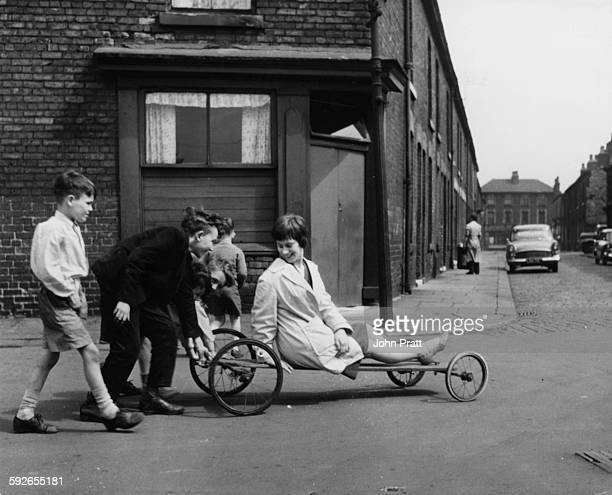 Actress Rita Tushingham being pushed around on a wheeled cart by a group of children filming scenes for 'A Taste of Honey' Liverpool 1960