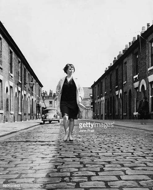 Actress Rita Tushingham walking down a terraced cobbled street filming scenes for 'A Taste of Honey' in Liverpool despite the film being set in...