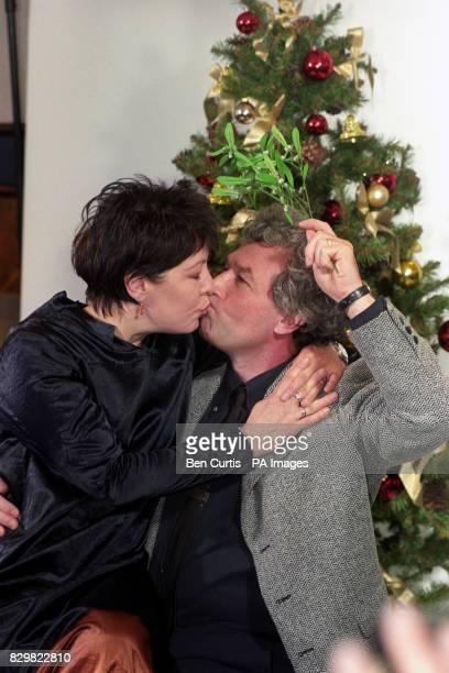Actress Roberta Taylor kisses Gavin Richards under the mistletoe