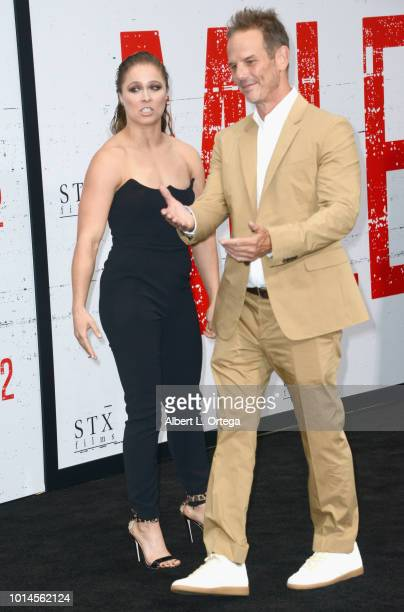 Actress Ronda Rousey and director Peter Berg arrive for the Premiere Of STX Films' 'Mile 22' held at Westwood Village Theatre on August 9 2018 in...