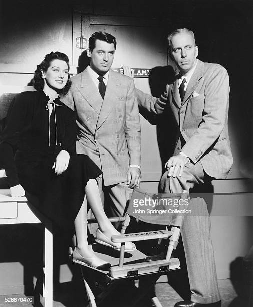 Actress Rosalind Russell sits beside actor Cary Grant and film director Howard Hawks as the trio watches Ralph Bellamy shoot a scene for his upcoming...
