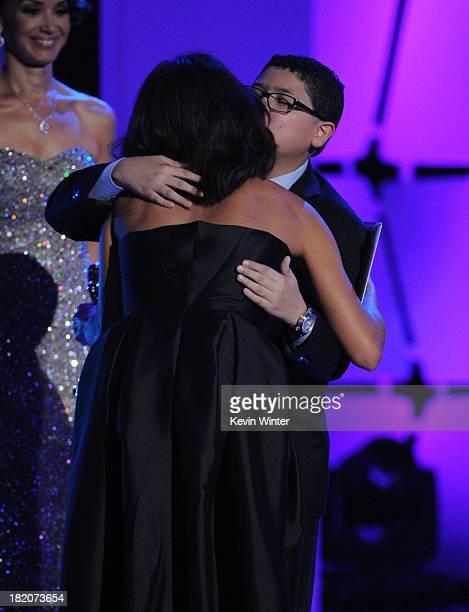 Actress Rosario Dawson accepts an award from presenter Rico Rodriguez onstage during the 2013 NCLR ALMA Awards at Pasadena Civic Auditorium on...