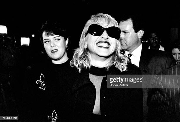 Actress Rosie O'Donnell looking askance at singer/actress Madonna who is giving a grimacing smile amongst others at premiere party for the movie A...
