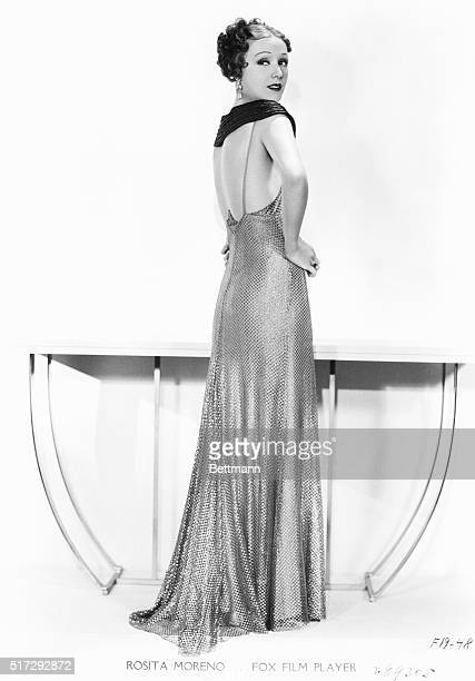 Actress Rosita Moreno wears a gold net gown designed by Fox Film stylist Lillian for the film Frontiers of Love