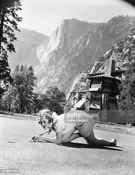 Actress Sally Eilers makes sure of her shot on the putting green in front of her lodge during her vacation at Yosemite National Park.