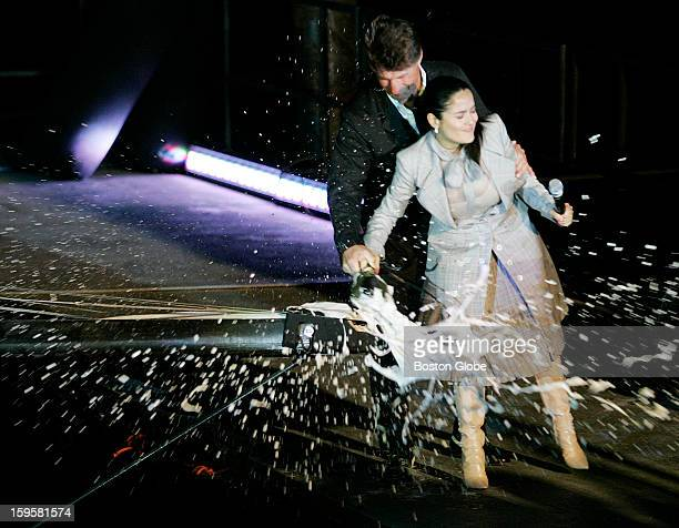 """Actress Salma Hayek, with the help of crew member Jerry Kirby, breaks a bottle of champaign on the bow of PUMA Ocean Racing's new boat christened """"il..."""