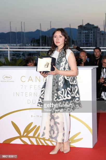 Actress Samal Yeslyamova poses with the Best Actress award for her role in 'Ayka' at the photocall the Palme D'Or Winner during the 71st annual...