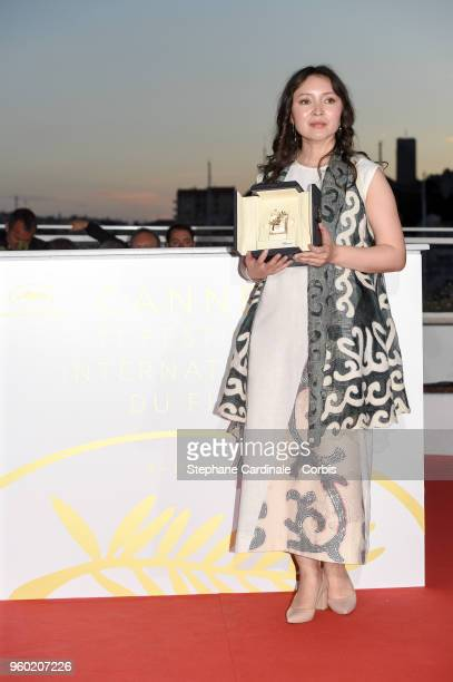 Actress Samal Yeslyamova poses with the Best Actress award for her role in 'Ayka' at the Palme D'Or Winner Photocall during the 71st annual Cannes...