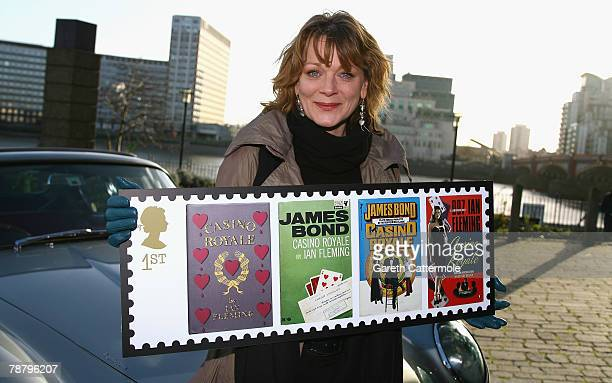 Actress Samantha Bond who played Miss Moneypenny in the James Bond films poses with an Aston Martin DB6 to launch a new set of stamps from The Royal...
