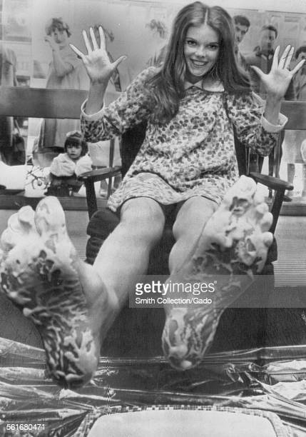 Actress Samantha Eggar makes impressions of her footprints in the foyer of a London theater August 11 1966
