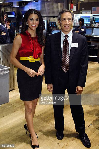 Actress Samantha Harris stands on the floor at the New York Stock Exchange with a NYSE employee on July 21, 2009 in New York City.