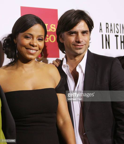 Actress Sanaa Lathan and actor John Stamos arrive at the Los Angeles premiere of 'A Raisin in the Sun' held at AMC Magic Johnson Theaters on February...