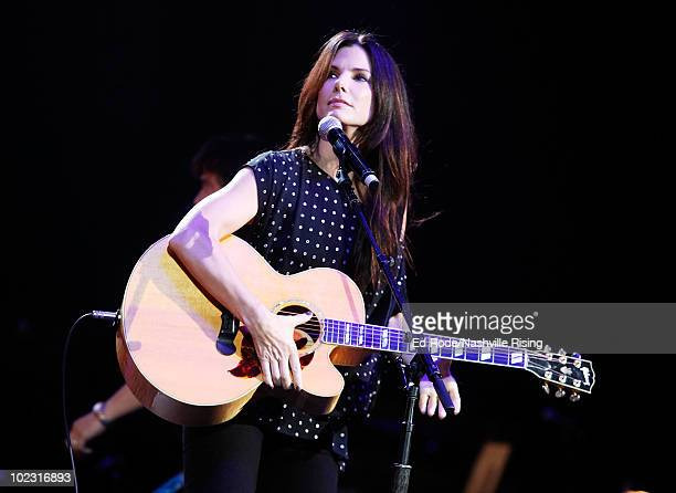 Actress Sandra Bullock performs onstage at Nashville Rising a benefit concert for flood relief at Bridgestone Arena on June 22 2010 in Nashville...