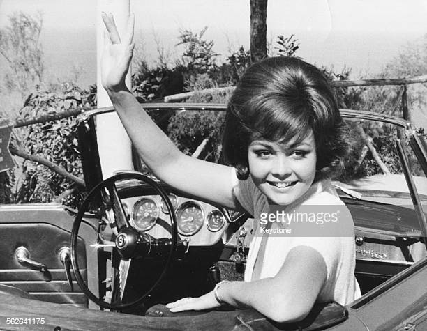 Actress Sandra Milo waving from her car in a scene from the film 'The Big Parasol' Rome October 1965