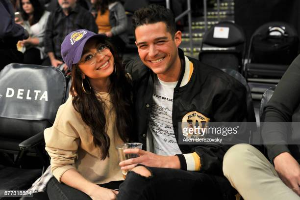 Actress Sarah Hyland and Wells Adams attend a basketball game between the Los Angeles Lakers and the Chicago Bulls at Staples Center on November 21...