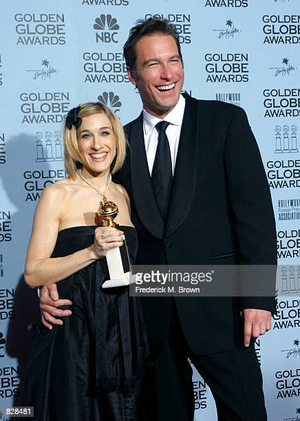 Actress Sarah Jessica Parker poses with actor John Corbett backstage during the 59th Annual Golden Globe Awards at the Beverly Hilton Hotel January...