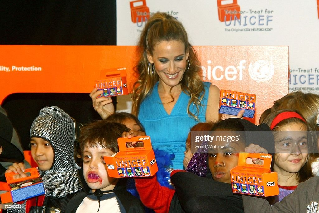 actress sarah jessica parker poses with children dressed in halloween costumes during the unicef halloween party