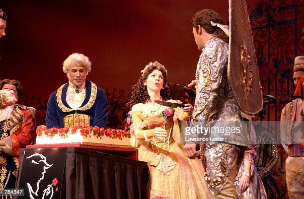 Actress Sarah Litzsinger as Belle asks ensemble player Christopher Monteleone as Cake Server to cut the cake to celebrate the 3225th performance of...