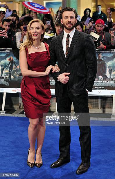 US actress Scarlett Johansson and US actor Chris Evans pose for photographs as they arrive to attend the UK premiere of Captain America The Winter...