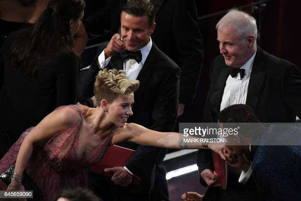 TOPSHOT US actress Scarlett Johansson is welcomed by US actor Terrence Howard as they arrive at the 89th Oscars on February 26 2017 in Hollywood...
