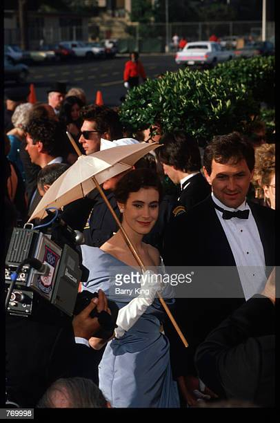Actress Sean Young holds a parasol while standing next to an unidentified man at the 1988 Academy Awards April 11 1988 in Los Angeles CA The Academy...