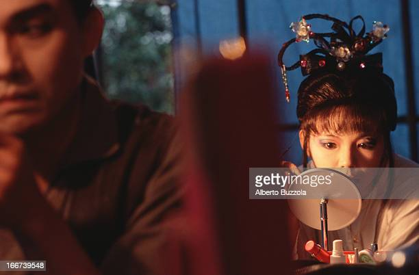 Actress Sh Huei Jun puts on her makeup before going onstage at the HoLo Taiwanese Opera House