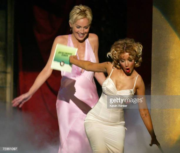 Actress Sharon Stone and singer Christina Aguilera who trips on her way present the award for 'BreakThrough Female' on stage at the 2004 MTV Movie...