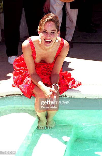 Actress Sharon Stone dips her feet in the pool during her sister Kelly Stones charity Planet Hope at Hal and Cynthia Gershams backyard June 26 1994...