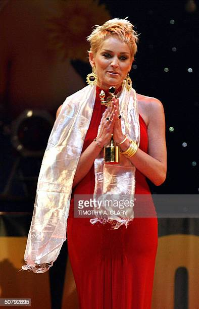 US actress Sharon Stone holds her award for Best Woman Consceness during the 2004 Bollywood Movie Awards at the Trump Taj Mahal 01 May 2004 in...