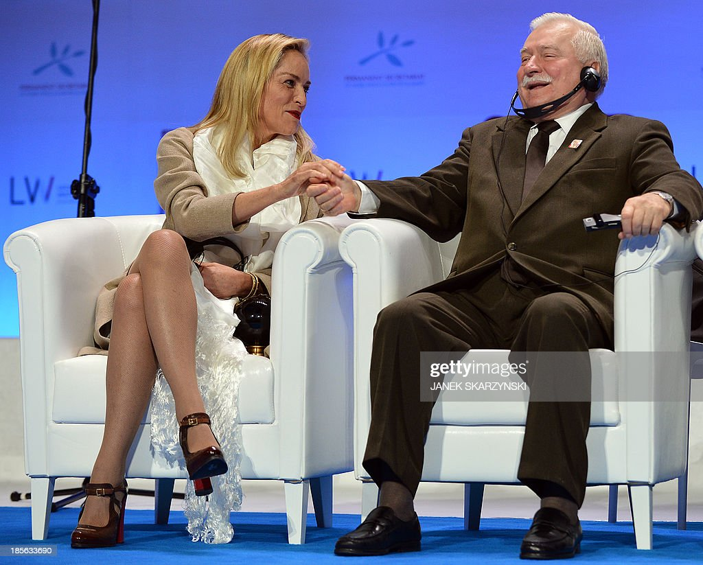 US actress Sharon Stone (L) shakes hands with Former Polish President and 1983 Nobel Peace laureate Polish Lech Walesa after she received the Peace Summit Award at the end of the World Summit of Nobel Peace Laureates on October 23, 2013 in Warsaw.